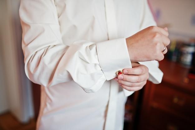 Hübscher bräutigam, der oben ankleidet und zu seiner hochzeitszeremonie fertig wird.