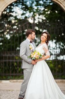 Hübscher bräutigam, der schöne braut mit blumenstrauß im romantischen europäischen park umarmt