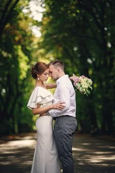 Hübscher bräutigam, der seine schöne atemberaubende braut mit blumenstrauß im romantischen europäischen park umarmt