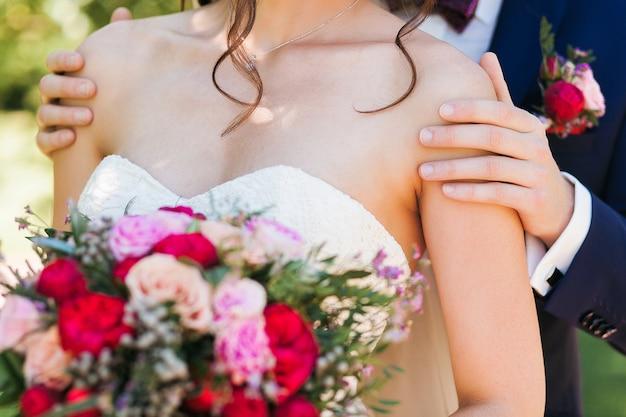 Hübscher bräutigam im dunkelblauen anzug, der leicht schöne braut mit brautblumenstrauß hält