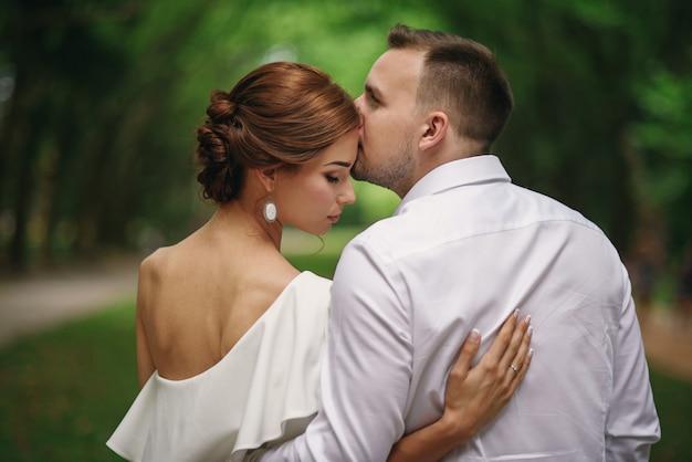 Hübscher bräutigam küsst zärtlich seine schöne frau auf einem spaziergang im park