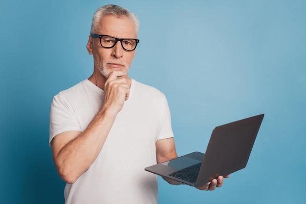 Hübscher brainstorming alter mann mit laptop auf blauem hintergrund isoliert