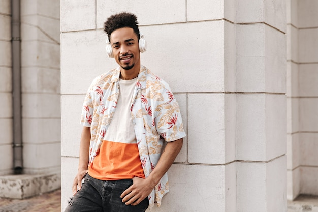 Hübscher brauner lockiger dunkelhäutiger mann in orangefarbenem t-shirt, geblümtem hemd und schwarzer jeans lehnt sich an die weiße wand und hört draußen musik über kopfhörer headphones