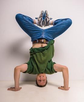 Hübscher breakdancer, der auf seinem kopf und händen steht.