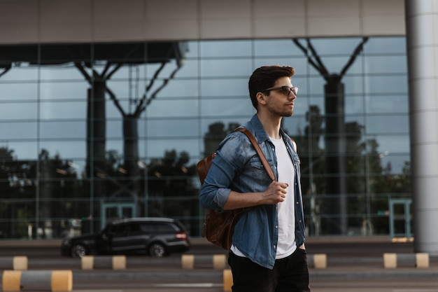 Hübscher brünette mann in jeansjacke, weißem t-shirt und schwarzer hose posiert draußen
