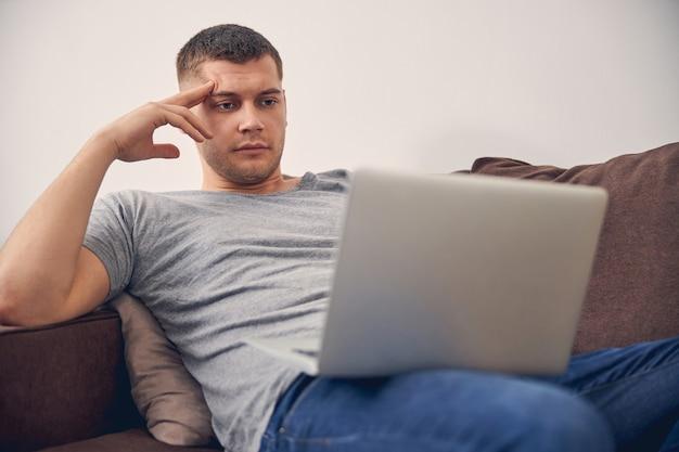 Hübscher brünette mann sitzt auf der couch und berührt seinen kopf während der arbeit