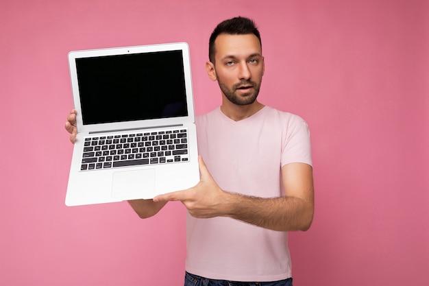 Hübscher brunet-mann, der laptop-computer hält und kamera im t-shirt auf isoliertem rosa hintergrund betrachtet.