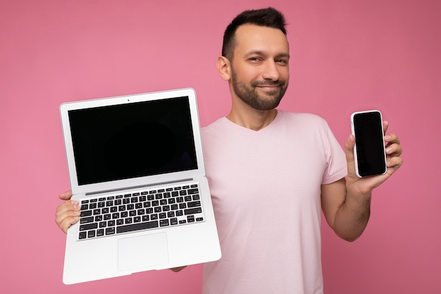 Hübscher brunet-mann, der laptop-computer und handy fischig betrachtet kamera hält
