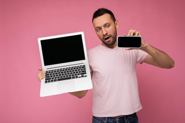 Hübscher brunet-mann mit offenem mund, der laptop-computer und handy hält, das telefon im t-shirt auf lokalisiertem rosa hintergrund betrachtet.
