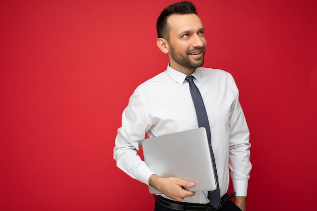 Hübscher brunetmann, der laptop-computer hält, der zur seite in weißem hemd und krawatte auf lokalisiertem rotem hintergrund schaut.