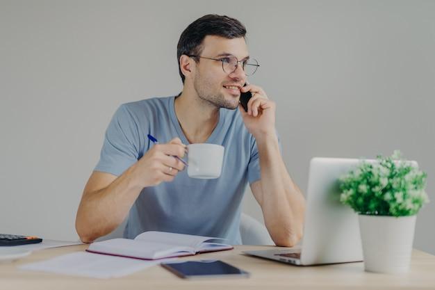 Hübscher brunetmann in den runden schauspielen und im zufälligen t-shirt, trinkt heißes getränk, hat telefongespräch