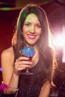 Hübscher brunette, der ein cocktail trinkt