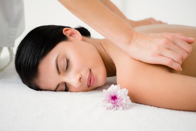 Hübscher brunette, der eine massage mit blume genießt