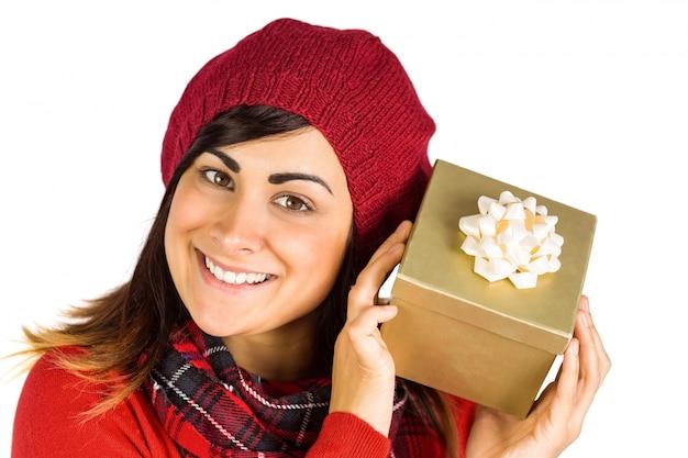 Hübscher brunette im hut, der ein geschenk hält