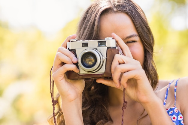 Hübscher brunette im park unter verwendung der retro- kamera
