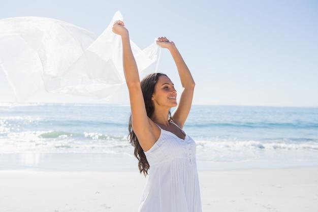 Hübscher brunette im weißen sonnenkleid, das sarong hält