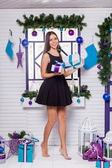 Hübscher brunette in einem schwarzen kleid auf einer weißen terrasse mit geschenken i