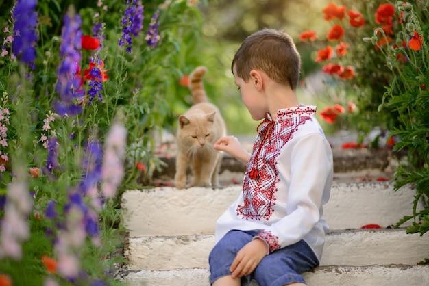 Hübscher brunettejunge 5-6 jahre alt in einem traditionellen kostüm auf einem mohnblumengebiet im sommer
