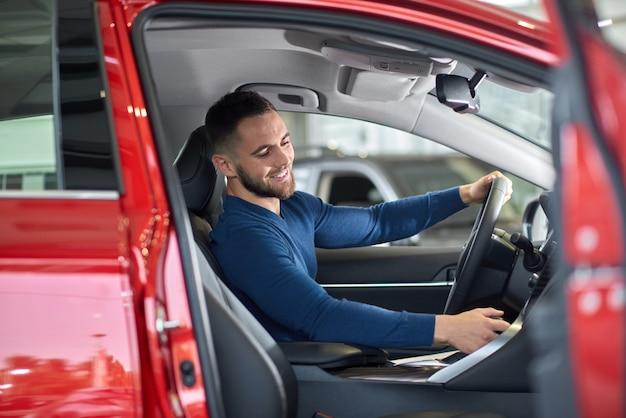 Hübscher brunettemann, der im roten auto mit geöffneter tür sitzt.
