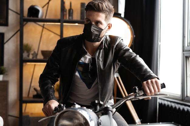 Hübscher brutaler männlicher biker in der schwarzen maske in der lederjacke, die auf dem motorrad sitzt und nach vorne schaut