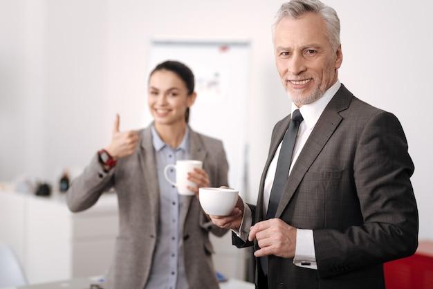 Hübscher büroangestellter, der graues kostüm hält tasse mit kaffee in der rechten hand trägt, während in halber position steht