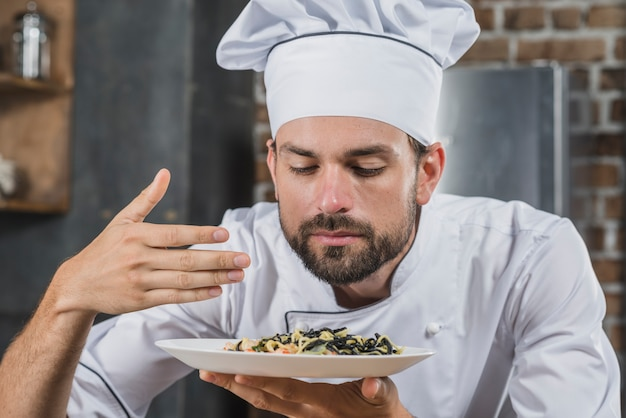 Hübscher chef, der geruch des gekochten tellers schnüffelt