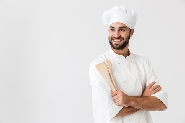 Hübscher chefmann in kochuniform, der lächelt, während er hölzerne küchenutensilien isoliert über weißer wand hält?