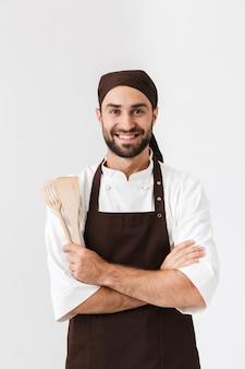 Hübscher chefmann in kochuniform, der lächelt, während er küchengeräte aus holz isoliert über weißer wand hält?