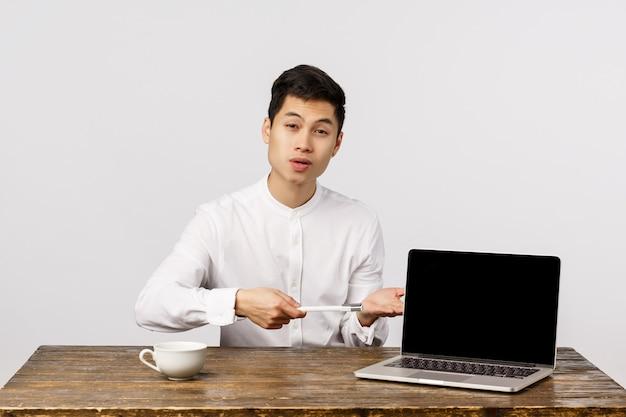 Hübscher chinesischer männlicher manager, büroangestellter stellen kundenunternehmensprodukt vor, zeigen diagramm auf laptopschirm, zeigen anzeige mit stift und erklären das konzept und sitzen