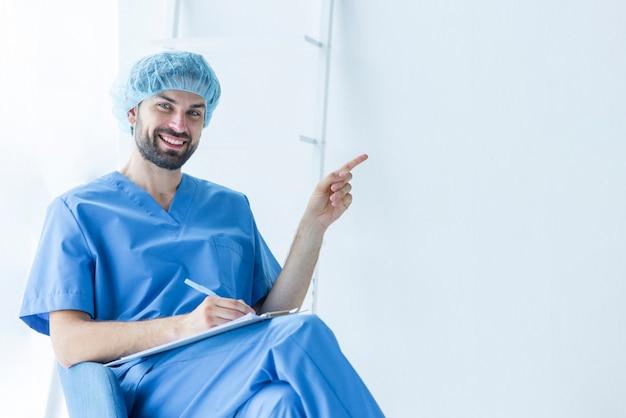 Hübscher chirurg mit dem klemmbrett, das auf leeren raum zeigt