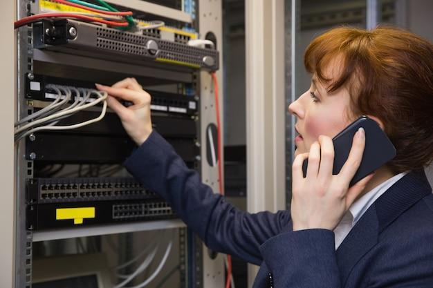 Hübscher computertechniker, der am telefon beim reparieren des servers spricht
