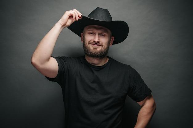 Hübscher cowboy, der schwarzen cowboyhut trägt