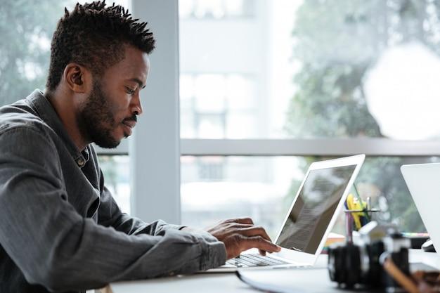Hübscher denkender ernster junger mann, der im büro coworking sitzt