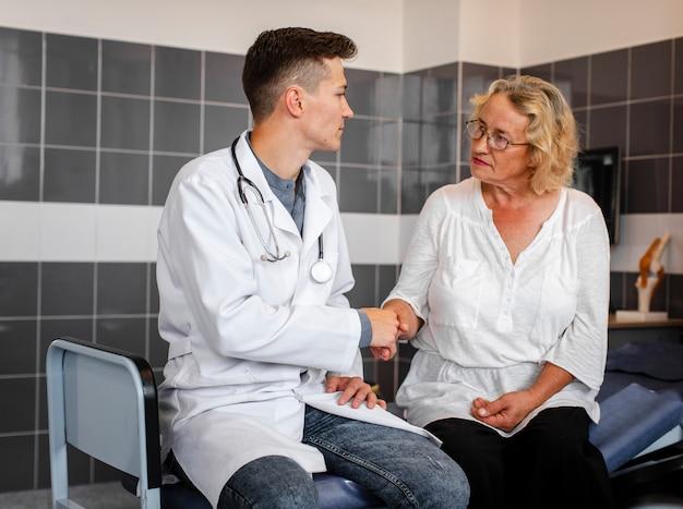 Hübscher doktor, der hand mit patienten rüttelt
