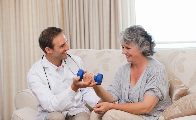 Hübscher doktor, der seinem patienten hilft, übungen zu tun