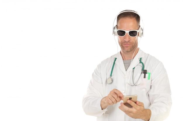 Hübscher doktor mit hörender musik der sonnenbrille mit kopfhörern