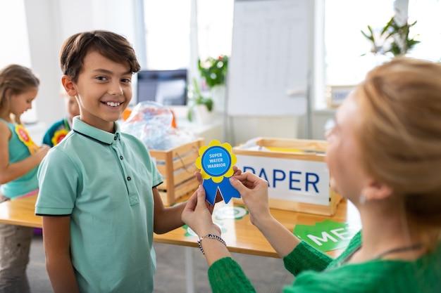 Hübscher dunkeläugiger junge, der sich zufrieden fühlt, während er in der schule eine belohnung bekommt