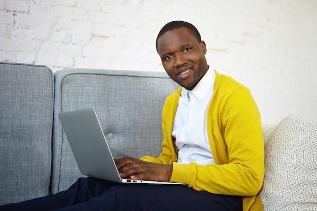 Hübscher dunkelhäutiger männlicher blogger in der gelben strickjacke, die auf generischem laptop-tastatur tastet, neuen beitrag auf seinem online-blog veröffentlicht, ausdruck inspiriert, schaut und lächelt
