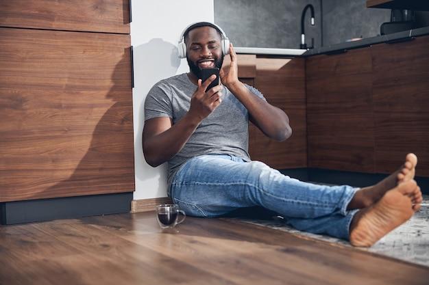 Hübscher dunkelhäutiger mann, der ein lächeln auf seinem gesicht behält, während er sein gerät für die online-kommunikation verwendet
