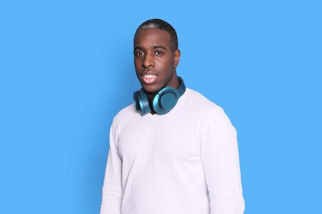 Hübscher dunkelhäutiger mann mit kopfhörern um seinen hals beim betrachten der kamera gegen blauen hintergrund