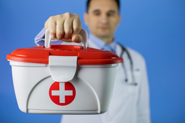 Hübscher dunkler haar 40s männlicher arzt hält rotes kreuz medizinische hilfeset