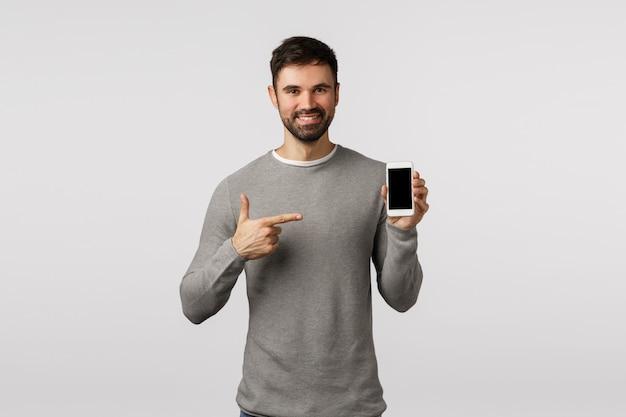 Hübscher durchsetzungsfähiger und angenehmer mann mit bart in der grauen strickjacke, fördern anwendung, filtern app, geräte und zeigen smartphoneanzeige und das lächeln erfreut, traf richtige wahl