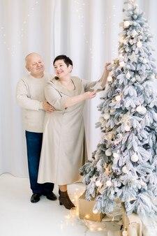Hübscher ehemann mittleren alters, der hwife im kleid umarmt, während er weihnachtsbaum verziert