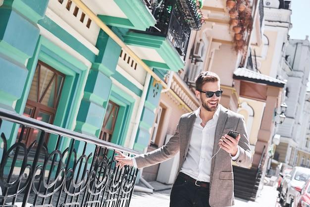 Hübscher eleganter junger mann auf der straße, der musik von seinem telefon hört