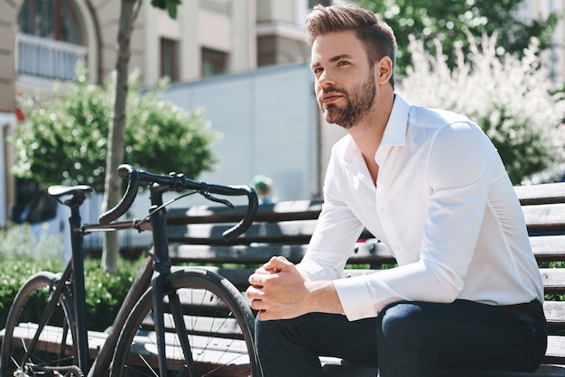 Hübscher eleganter junger mann sitzt auf der bank und entspannt und denkt in der öffentlichkeit