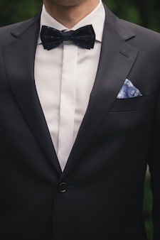 Hübscher eleganter junger modemann im klassischen anzugskostüm und -fliege des smokings.