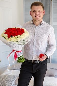Hübscher eleganter kerl im hemd, der einen ehering und rosen hält