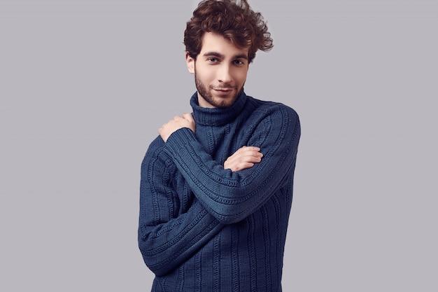 Hübscher eleganter mann mit dem gelockten haar in der blauen strickjacke