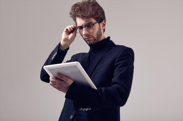 Hübscher eleganter mann mit tragendem anzug und gläsern des gelockten haares
