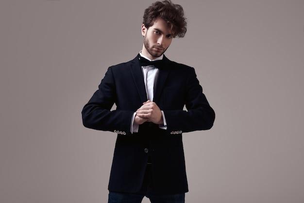 Hübscher eleganter mann mit tragendem smoking des gelockten haares